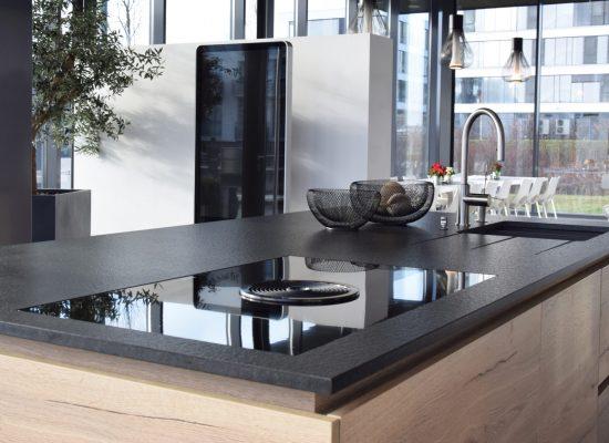 Ausstellungsküche von Küche und Wohnen in Holzgerlingen, Modell Paso, Hersteller Eggersmann. Kochinsel, Holzfronten, schwarze Oberflächen.