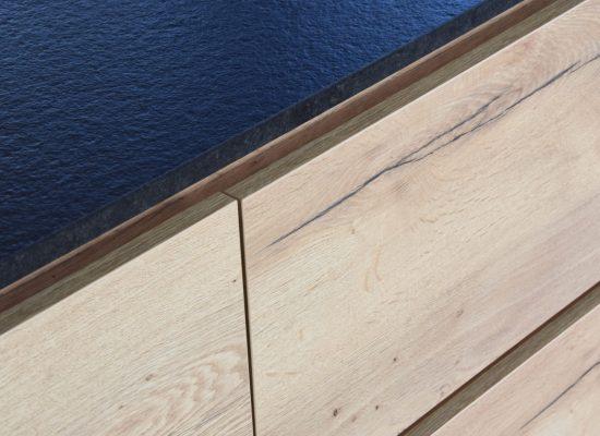 Detailansicht Schubladenfront, Front in Holz, Oberfläche in schwarzem Stein